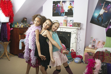 Happy young girls striking a pose in trendy bedroom at slumber Party