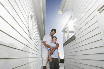 Portrait of happy father standing arm around son in narrow passageway between houses