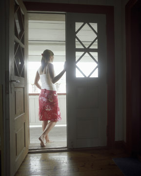Full length rear view of a young woman standing in open door