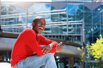 young black man laughing in the city with mobile phone