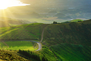 A panoramic sunset valley with road among the green hikes