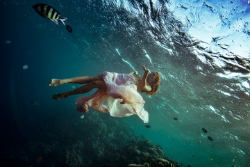 A model underwater in golden pink dress surrounded by small fish on deep blue ocean marine background