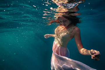 A model underwater in golden pink dress on deep blue ocean marine background
