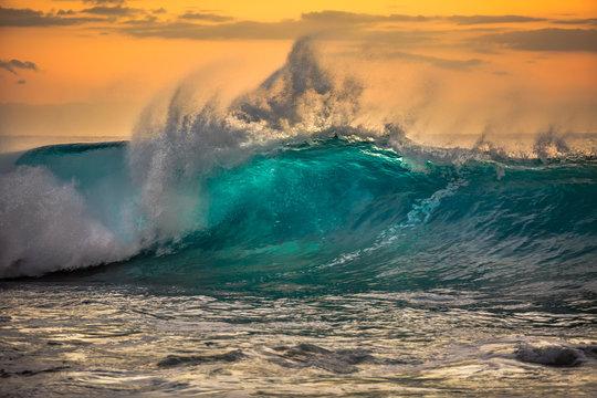 Green blue ocean splashing wave in front of orange sunset sky background