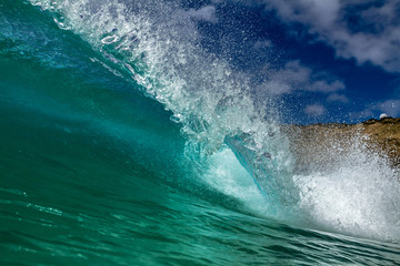 Bright clear blue ocean crashing breaking wave barrel for surfing lessons