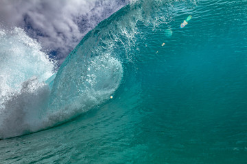 Bright clear blue ocean wave barrel for surfing lessons