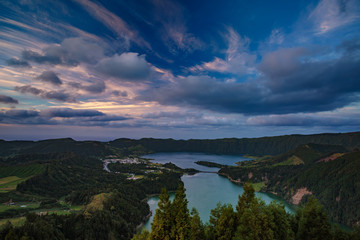 Mountain landscape in green valley with green lake in Azores island mountains with beautiful clouds at sunset time
