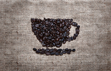 Picture of Coffee in a cup shape. Macro closeup of coffee-beans, brown food background, grid fabric burlap sackcloth
