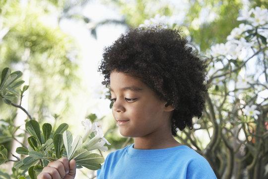 Closeup of cute boy smelling flowers in garden