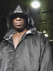 Portrait of an African American boxer wearing robe with hood up