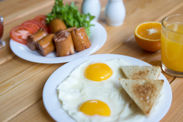 Orange juice, Two eggs and sausage for healthy breakfast.