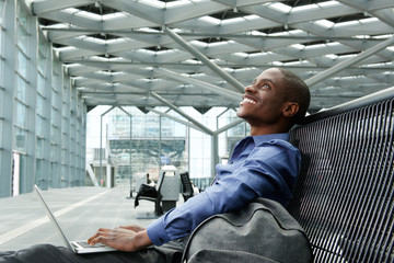 happy young businessman sitting with laptop at station