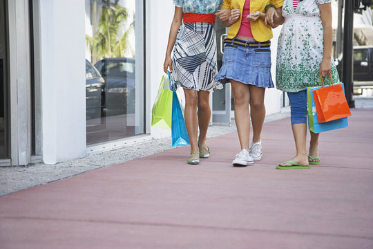 Low section of three teenage girls with shopping bags walking on pavement