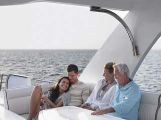 Happy young and middle aged couples relaxing on yacht