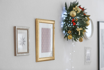 Pictures and beautiful Christmas wreath hanging on wall