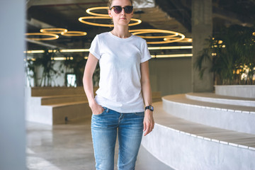 Front view.Young woman in sunglasses,white t-shirt and blue jeans standing in room with modern interior, with his hand in pocket of jeans. Mock up.In background, seating and lighting in form of rings.