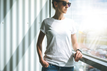 Front view. Young woman in sunglasses,white t-shirt and jeans standing near window in room, with his hand in pocket of jeans. In background white wall. Girl looks out window.Mock up.
