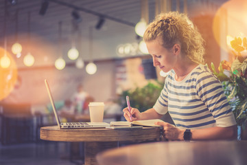 Side view. Young woman in striped blouse sitting at table in coffee shop and makes notes in notebook. In front of her is laptop next to cup of coffee. Online learning. Student doing homework.