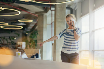 Young woman in striped shirt standing in room with modern interior and talking on cell phone while pointing at laptop screen. Nearby cup of coffee. Ceiling lights in form of rings.Girl uses gadget.