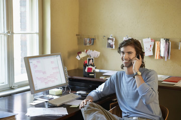 Portrait of a smiling young man using cellphone by computer in the office