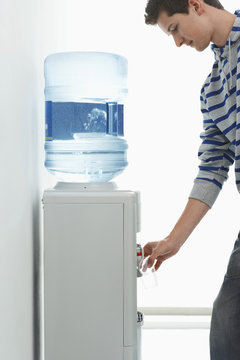 Side view of a young man pouring water from cooler