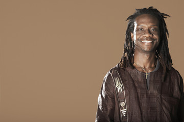 Portrait of African American man with dreadlocks smiling on brown background