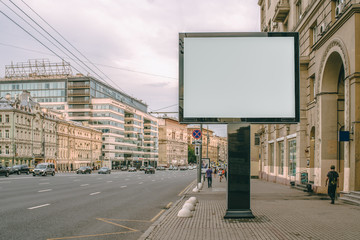 Horizontal blank billboard on the city street. In background buildings and road with cars. Mock up.