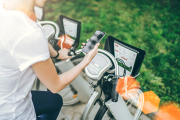 Summer day, view from behind. Close-up of smartphone with blank screen in hand of young woman in white t-shirt sitting on city bike.Girl pays with smartphone rent bicycle. Digital gadget.
