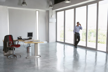 Full length of a male executive using cellphone against glass wall in empty office