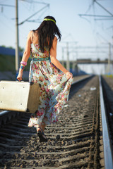 beautiful girl with a suitcase walking on railroad tracks