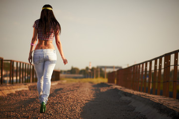 Beautiful girl in jeans walking on the road