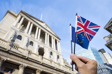 Hand holding European Union and British Union Jack flags in front of the Bank of England as symbols of the financial repercussions of the Brexit EU referendum