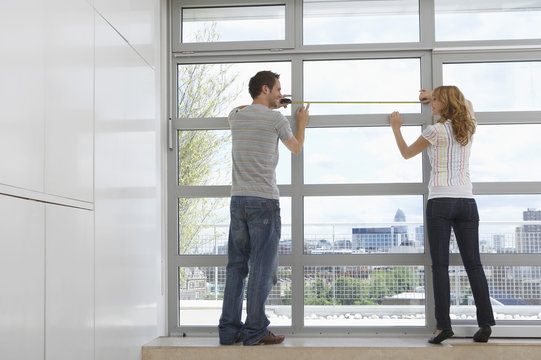 Full length rear view of young couple measuring window in modern apartment