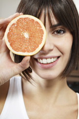 Closeup of a smiling young woman holding half of grapefruit in front of face
