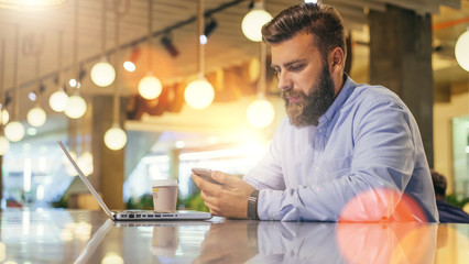 Side view.Young bearded businessman wearing in blue shirt,sitting at table in cafe and use smartphone.Nearby is laptop and cup of coffee.Man checks messages on digital gadget.Guy looks screen of phone