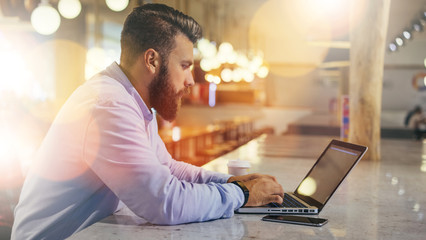 Side view.Young bearded businessman wearing blue shirt,sitting at table in cafe and uses laptop.Nearby is smartphone and cup of coffee. Man checks email on computer. Freelancer working outside office.