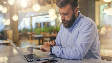 Side view.Young bearded businessman wearing blue shirt, sitting at table in cafe and uses smartwatch. Nearby is laptop, smartphone and cup of coffee. Man checks messages on digital gadget.Film effect.