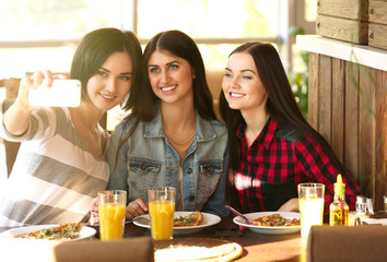 Cheerful young women taking selfie in pizzeria