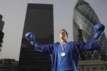 Male boxer wearing gold medal in front of downtown skyscrapers in London