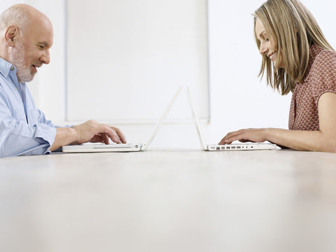 Side view of a mature man and woman using laptops on table