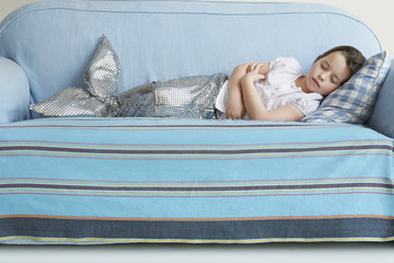 Young girl in mermaid costume sleeping on sofa at home