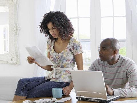 African American couple sitting at table using laptop and reading document