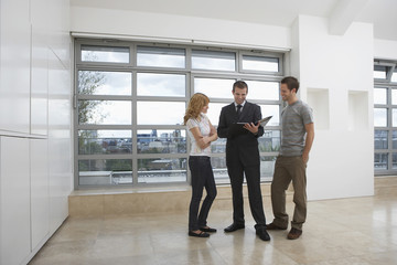 Full length of a real estate agent showing couple new apartment