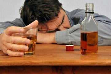 Homme ivre endormi sur une table avec un verre de whisky en main