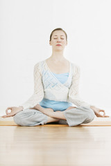 Full length of fit woman meditating in lotus position at gym