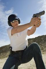 Female officer aiming hand gun at firing range in desert