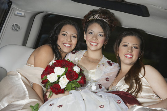 Portrait of a beautiful Quinceanera sitting with two female friends in Limousine