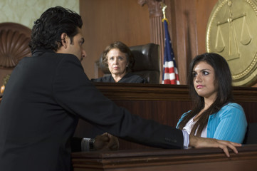 A lawyer questioning a witness in front of female judge in a courtroom.