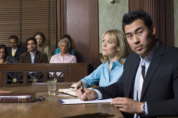 Portrait of a male defense lawyer sitting with client in courtroom