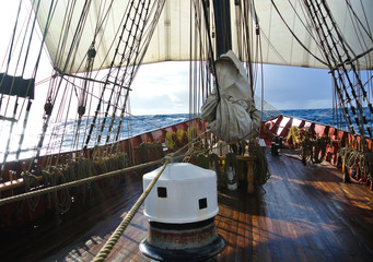 On deck with capstan and sails of a traditional tallship or sailboat